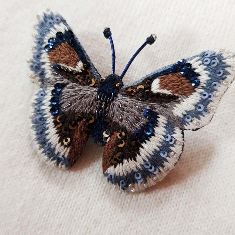 Broche artisanale d'un papillon gris, brodée à la main, broderie et perles